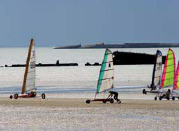 Wind surfing on a stretch of sandy beach in Normandy